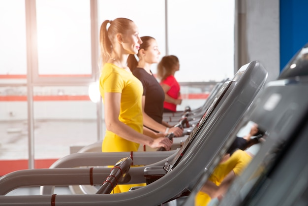 Group of young women running on treadmills in modern sport gym