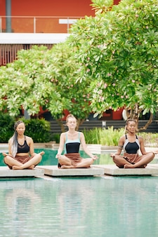 Group of young women sitting on stones in swimming pool in lotus position when meditating in the morning
