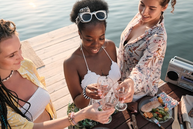 Group of young women toasting with glasses of white wine while spending time on a pier outdoors