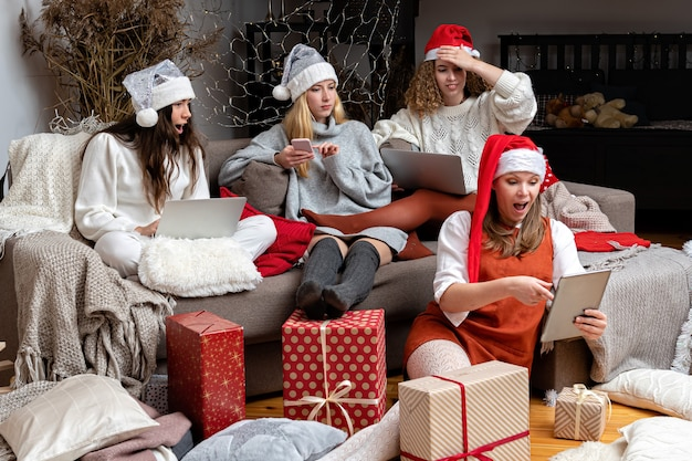 Group of young women wearing christmas hats make greeting video calls at christmas time