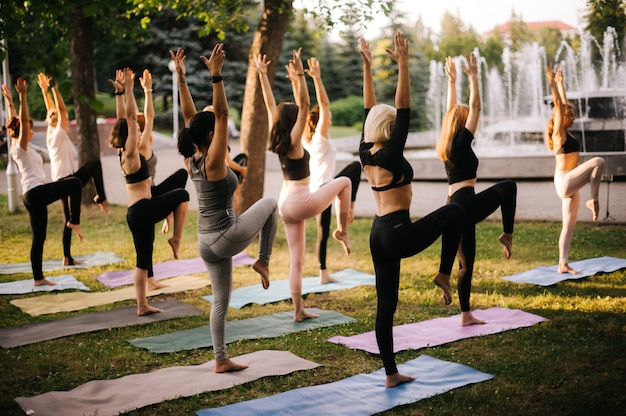 Group of young yogini women are exercising yoga pose in city park sunny beauty morning in background of fountain.