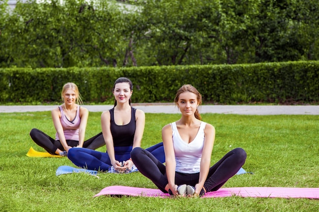 Groupe of beautiful healthy slimy women doing exersices on the green grass in the park, siting on mat in lotus poses and meditation, looking at camera. outdoor, sport lifestyle, yoga time, wellness