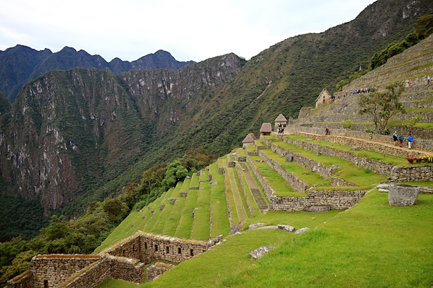 ペルーのクスコ地方にあるマチュピチュインカの城塞を探索する訪問者のグループ
