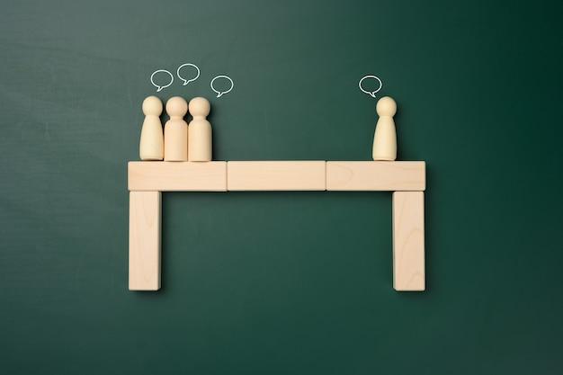 Группы деревянных фигур людей стоят друг напротив друга. концепция конфликта интересов, построение диалога, компромиссные решения