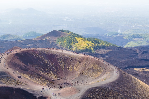 Groups of tourists walking along etna mountain. sicily, italy