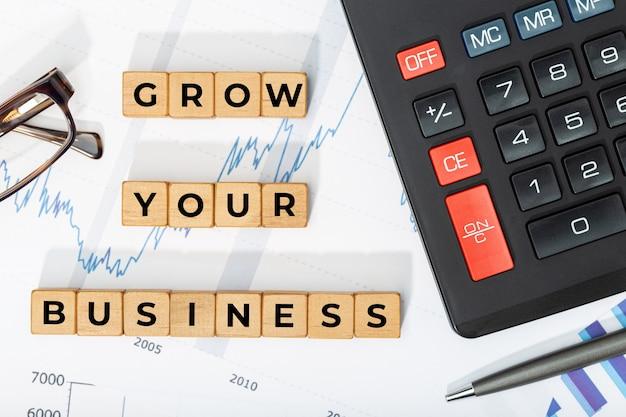 비즈니스 개념을 키우십시오. 문구, 계산기 및 인쇄 문자가있는 나무 블록