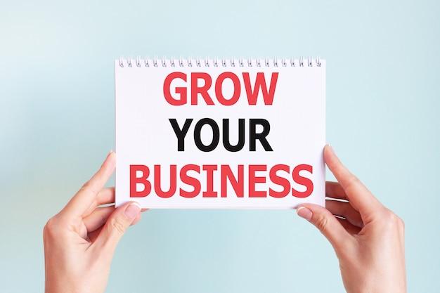 여자의 손에 흰색 카드 종이 시트에 비즈니스 단어 비문을 성장 시키십시오. 흰 종이에 검정과 빨강 글자. 비즈니스 개념.