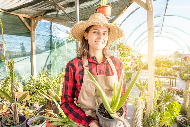 温室でアロエ植物を育てる。笑顔のプロの若い女性