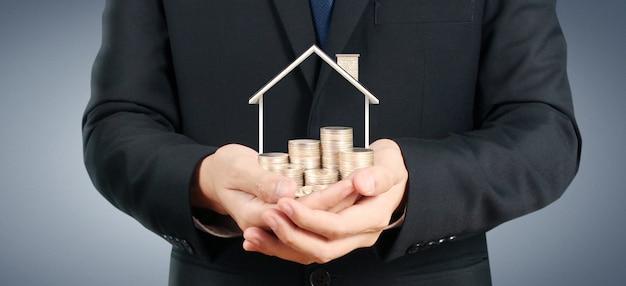 手にスタックコインの成長しているコインの家。投資物件の概念