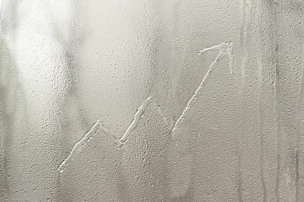 Growing graph on frosty window glass. business concept
