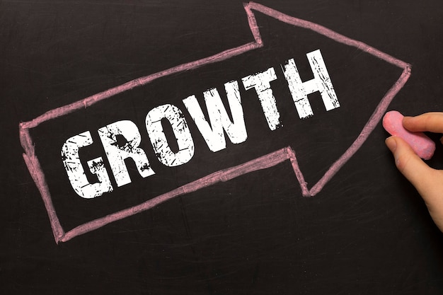 Growth - arrow with text and female hand with chalk