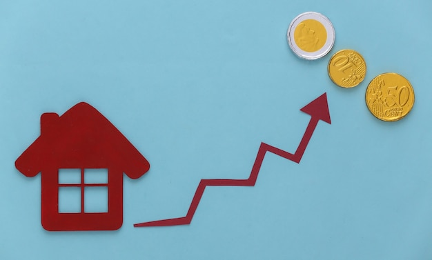 Growth in housing prices. house figurine and growth arrow tending upwards on a blue with coins