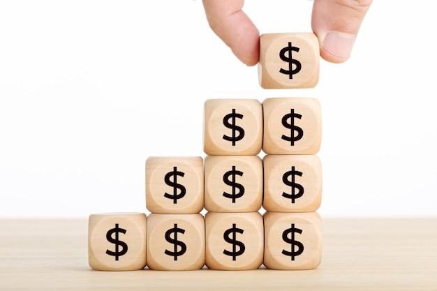 成長、貯蓄、富または豊かさの概念。木製のブロックとドル記号が積み重ねられたブロックを持っている手。スペースをコピーします。