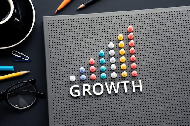 비즈니스 테이블에 핀 장식 차트가있는 성장 텍스트
