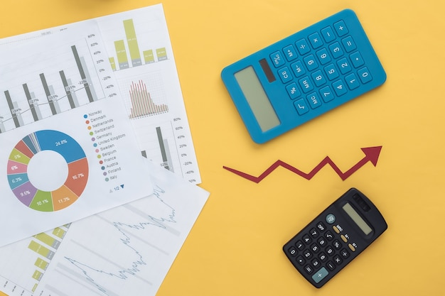 Growth upward arrow, graphs and charts and calculator on yellow