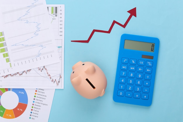 Growth upward arrow, graphs and charts, piggy bank and calculator on blue. business success