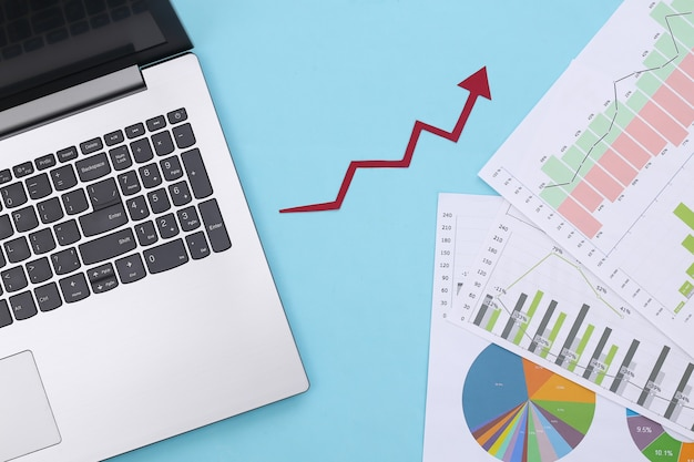 Growth upward arrow, graphs and charts with laptop on a blue