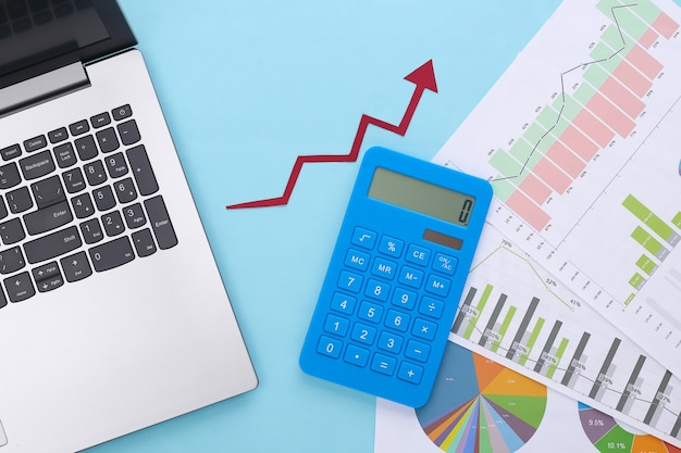 Growth upward arrow, graphs and charts with laptop and calculator on blue