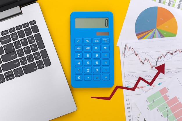Growth upward arrow, graphs and charts with laptop and calculator on yellow. online business. business success