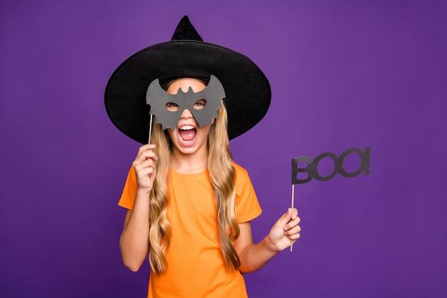 Grr! 작은 마녀 아가씨의 사진 박쥐 종이 스틱을 들고 초자연적 인 역할 할로윈 테마 파티 무서운 표정 착용 오렌지 티셔츠 마법사 모자 격리 된 보라색 배경