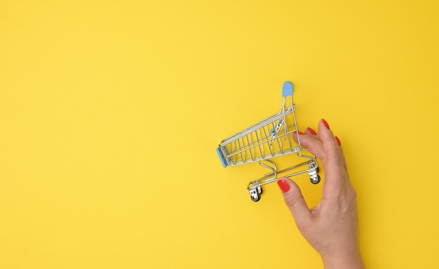 Grubby hands hold an empty metal miniature trolley on a yellow background. sale concept, seasonal discounts, copy space