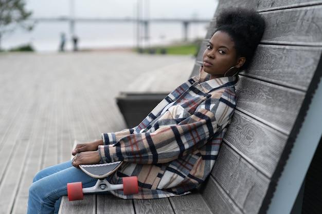 피곤한 아프리카 여성은 롱보드가 불행하고 회의적인 표정으로 도시 우주 공원에 앉아 있다