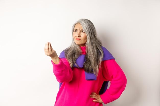 Сварливая азиатская бабушка жалуется, показывает итальянцу, какой жест вы хотите, трясет пальцами и сердито смотрит влево на место для копирования, стоя на белом фоне