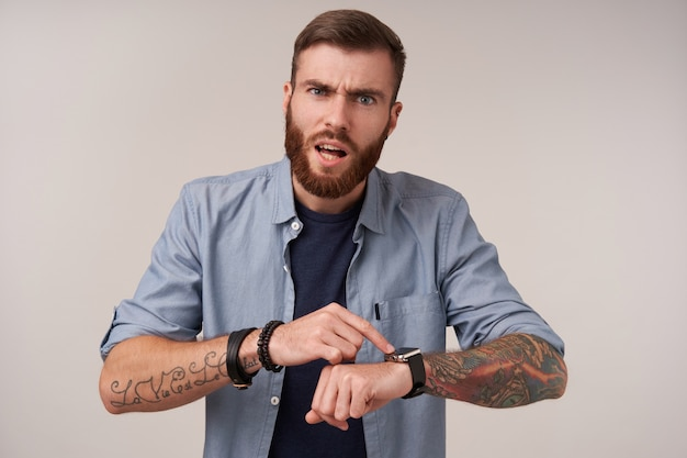 Grumpy blue-eyed brunette tattooed man with beard frowning his eyebrows while posing on white, pointing to his watch and looking angrily