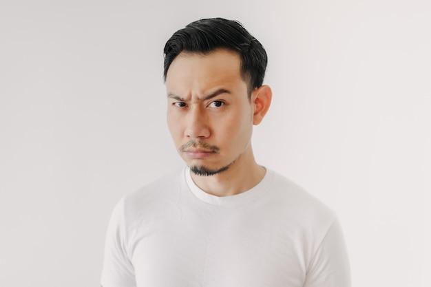 白い背景で隔離の白いtシャツの不機嫌そうな顔の男