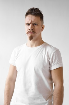 Grumpy hipster man with stylish mustache and beard frowning and staring at camera with angry facial expression, being dissatisfied with quality of product or service. negative human reaction