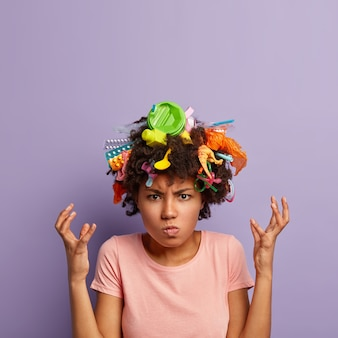 Grumpy outraged woman posing with garbage in her hair