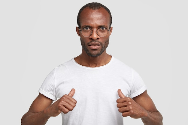 不機嫌そうな真面目な男は、多くの義務があることに驚いて、スタジオの壁に隔離されたカジュアルな白いtシャツを着て、自分自身を指しています