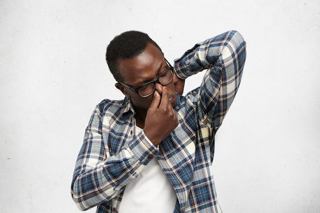 メガネとシャツを着た不機嫌な臭い若い浅黒い肌の男性