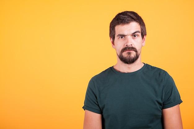 Grumpy는 카메라를 바라보는 노란색 배경의 걱정스러운 남자를 강조했습니다. 우울증, 불행, 스트레스 컨셉 이미지
