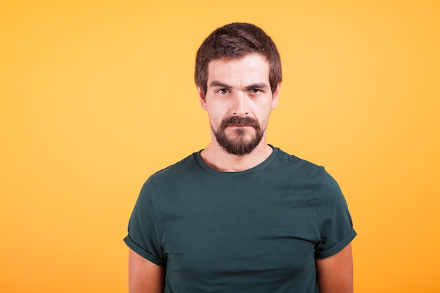 Grumpy stressed worried man on yellow background lookin at the camera. depression, unhappy and stress concept image