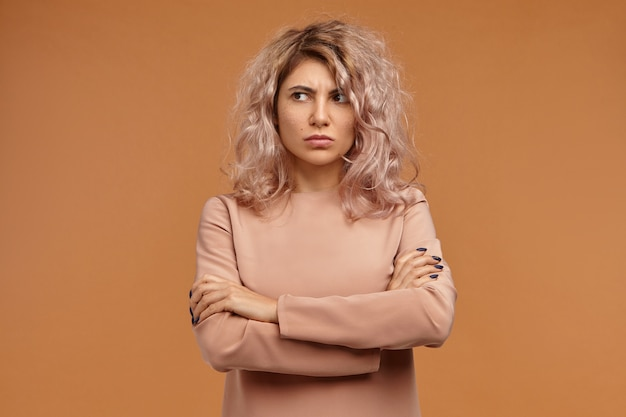 Grumpy stubborn hipster girl with voluminous hair expressing disrespect and indifference, not talking to you, looking away with displeased facial expression