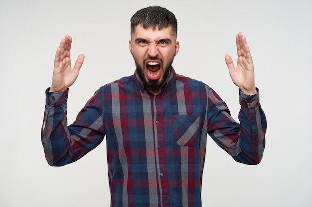 Grumpy young handsome short haired bearded male dressed in casual wear screaming angrily with wide mouth opened and raising hands emotionally, isolated over white wall