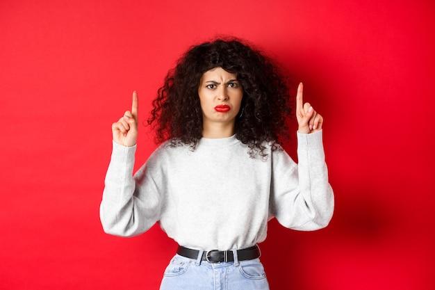 不機嫌そうな若い女性は、巻き毛が眉をひそめ、顔をゆがめ、不満を抱き、何か悪いことに指を向け、会社に不平を言い、赤い背景