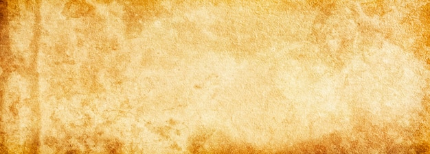 Grunge background banner of old brown paper in spots and streaks for design and text