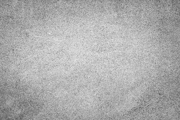 花崗岩に似た小さなドットの形でビネットと多孔質のテクスチャを持つグランジコンクリートの背景。