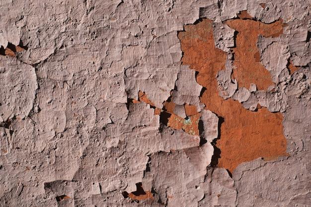 Гранж текстуры трещины краска. крупный план старой красной краской на стене на открытом воздухе. шероховатая поверхность фона.