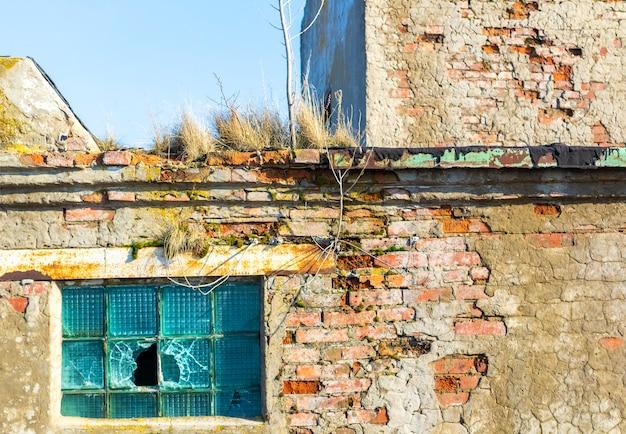 Grunge damaged broken windows in brick ruined building wall