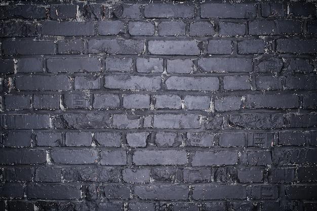 Grunge dark gray brick wall as background.