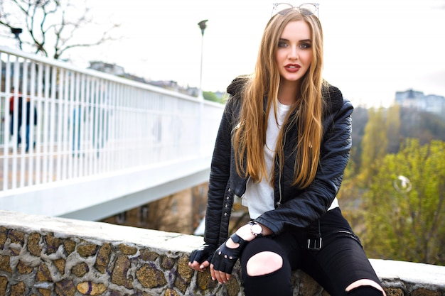 Grunge fashion portrait of stylish blonde woman, leather biker jacket and gloves, rock n roll mood, urban view on city bridge, street fashion, hairstyle make up, traveler.