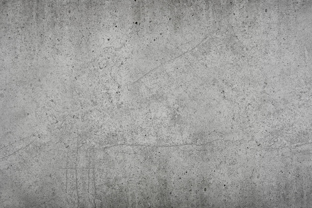 Grunge grey uneven stone texture background with cracks and stains