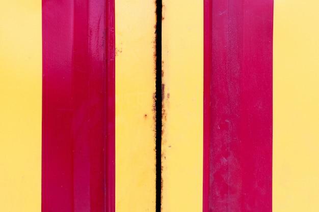 노란색과 빨간색 세로 줄무늬와 그런 지 강철 문. 금속 경계에서 금속 부식.