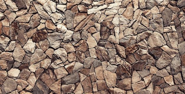グランジ石の壁。背景の古い岩壁のテクスチャ。背景またはテクスチャとしての石の壁。