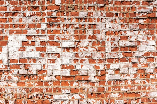 Grunge texture of abandoned building wall made with red bricks covered with white stucco at bright sunlight extreme closeup. traditional architectural style