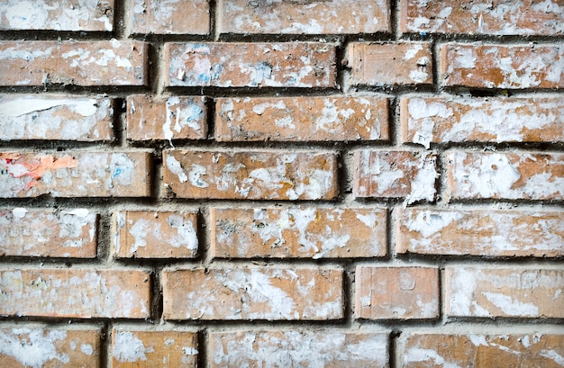 Grunge textured background of brick wall with torn  sticked papers