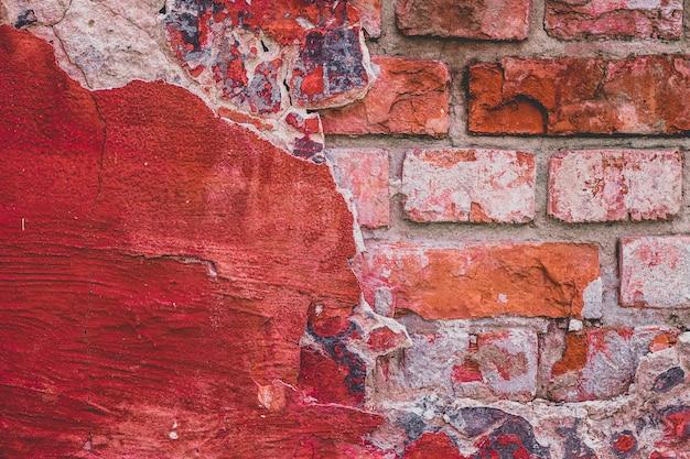 グランジのヴィンテージのレンガの壁の質感と白いスタッコの建物のファサード。